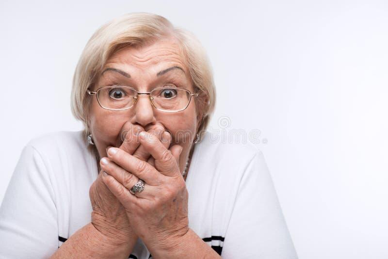 La mujer mayor se cierra boca, los oídos y los ojos con fotos de archivo libres de regalías