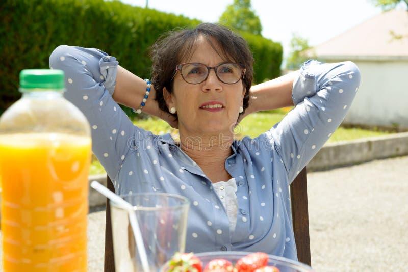 La mujer mayor se relaja en su jardín fotos de archivo