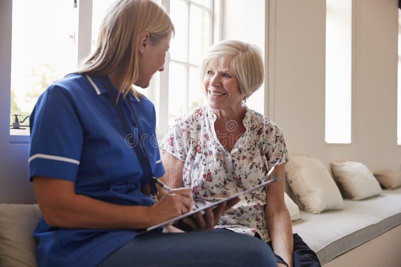 La mujer mayor se sienta con la enfermera que hace notas en la casa de retiro fotos de archivo libres de regalías