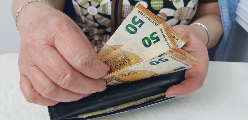 La mujer mayor se sostiene en el dinero euro del efectivo de las manos que lo pone en la cartera imagen de archivo