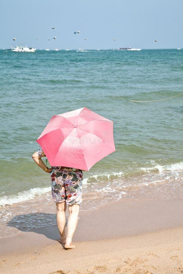 La mujer mayor se vistió en pantalones cortos con un paraguas rosado que se colocaba en una arena de la playa foto de archivo libre de regalías