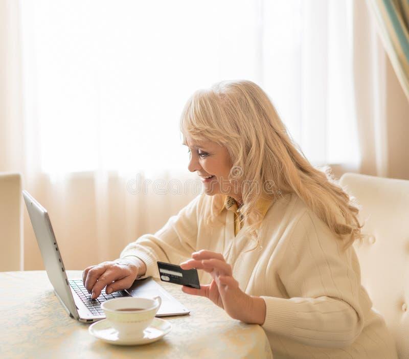 La mujer mayor sonriente utiliza el ordenador portátil y la tarjeta de crédito mientras que se sienta en la tabla fotos de archivo