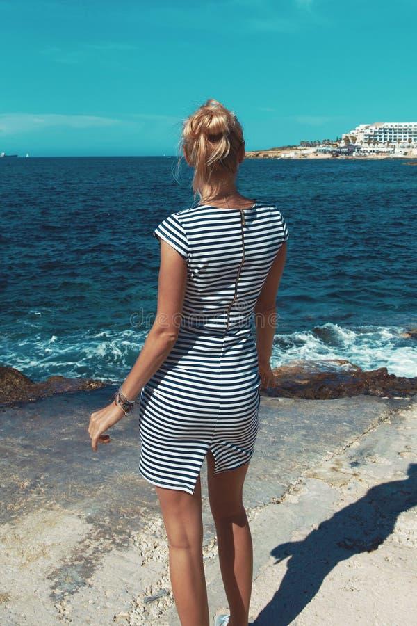 La mujer mediterránea atractiva joven que presenta en la parte posterior rocosa de la costa compite imagen de archivo libre de regalías