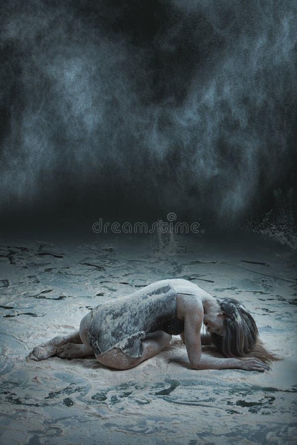 La mujer miente en el piso asperjado con la harina fotografía de archivo libre de regalías