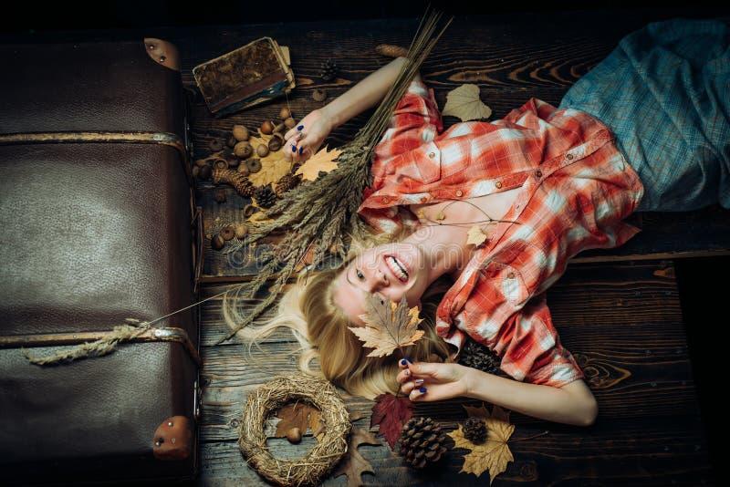 La mujer miente en fondo de madera de la hoja Concepto feliz de la gente del otoño Mujer joven atractiva en ropa estacional de un imágenes de archivo libres de regalías