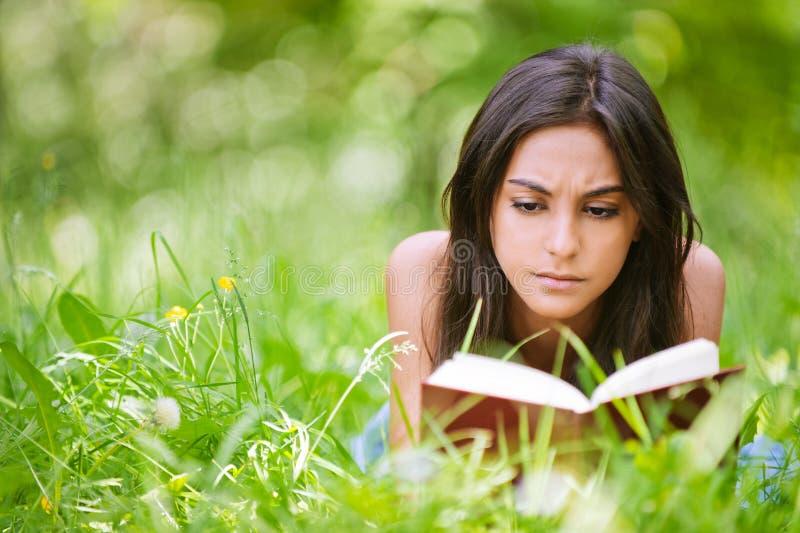 La mujer miente en hierba y lee el libro imágenes de archivo libres de regalías