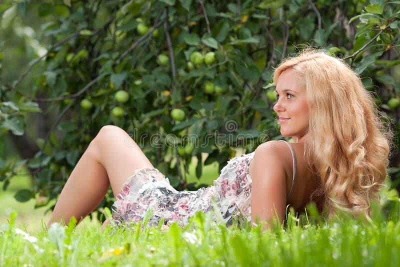 La mujer miente en una hierba foto de archivo