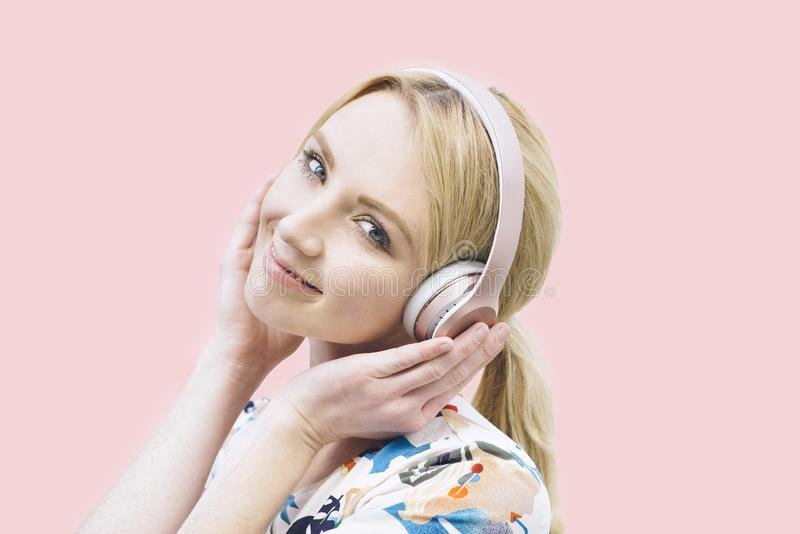 La mujer milenaria con el pelo rubio escucha los auriculares y las sonrisas fotos de archivo