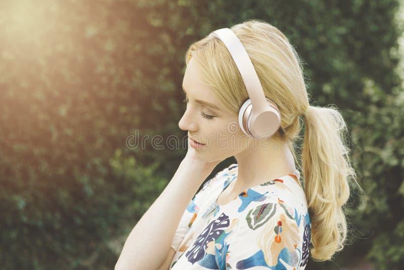 La mujer milenaria escucha la música en sus auriculares y se mueve emocionalmente imagenes de archivo