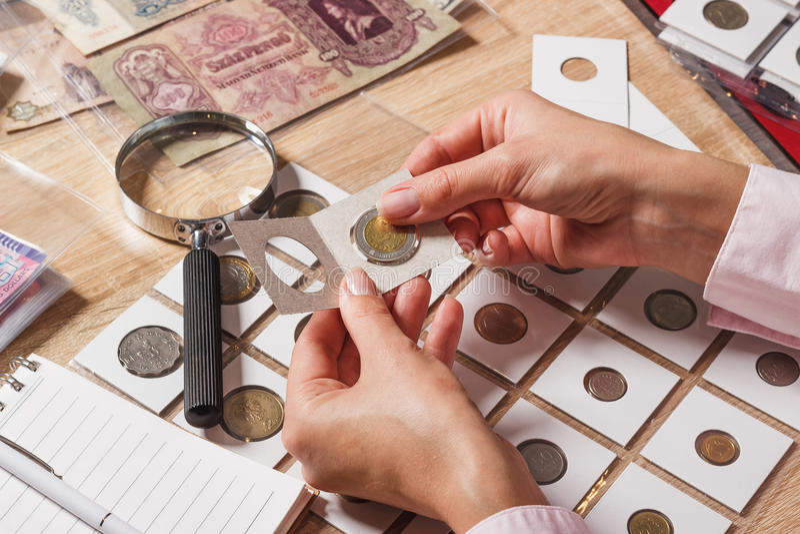 La mujer mira la moneda del colector s imagen de archivo