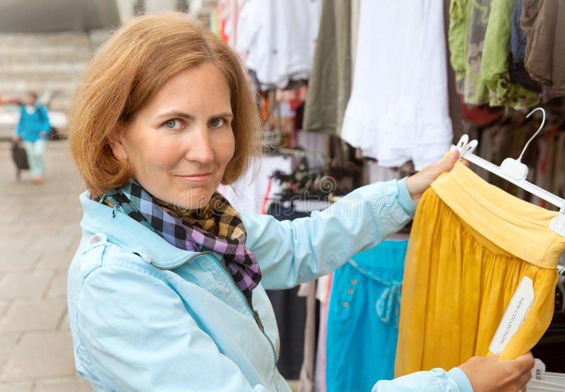 La mujer mira la ropa en mercado fotos de archivo