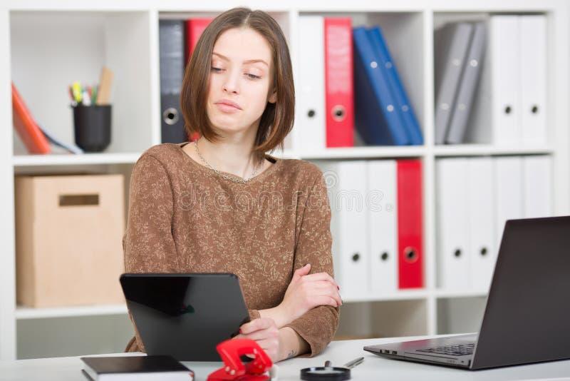 La mujer mira a través de redes sociales en la oficina La valoración mira en la exhibición de la tableta Una ceja aumentada para  imagen de archivo libre de regalías
