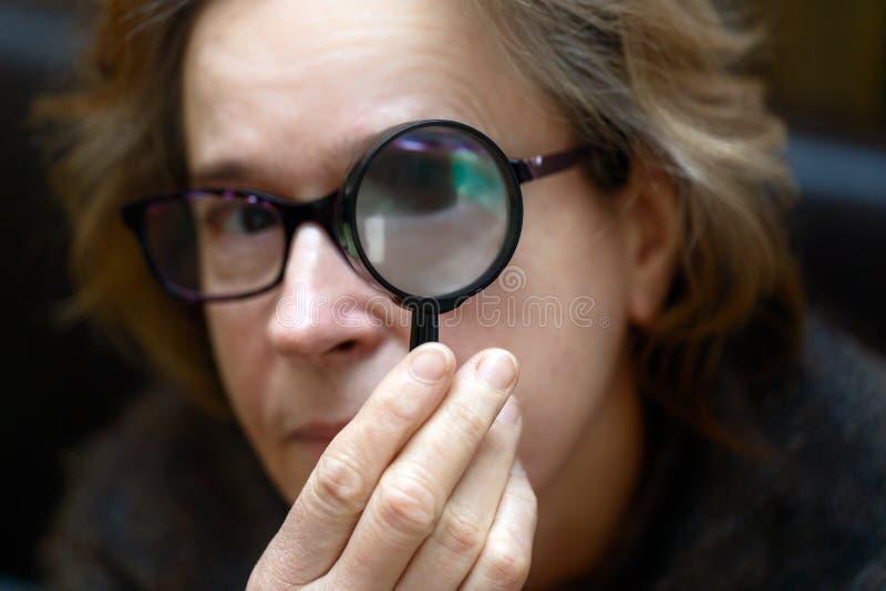 La mujer mira a través de una lupa foto de archivo libre de regalías
