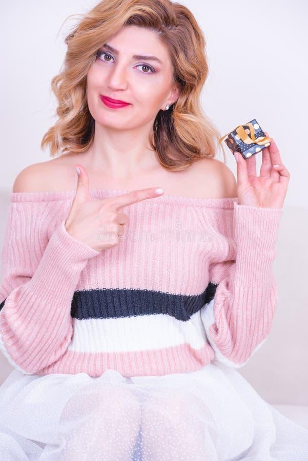 La mujer modelo hermosa atractiva sostiene la pequeña caja de regalo fotos de archivo libres de regalías