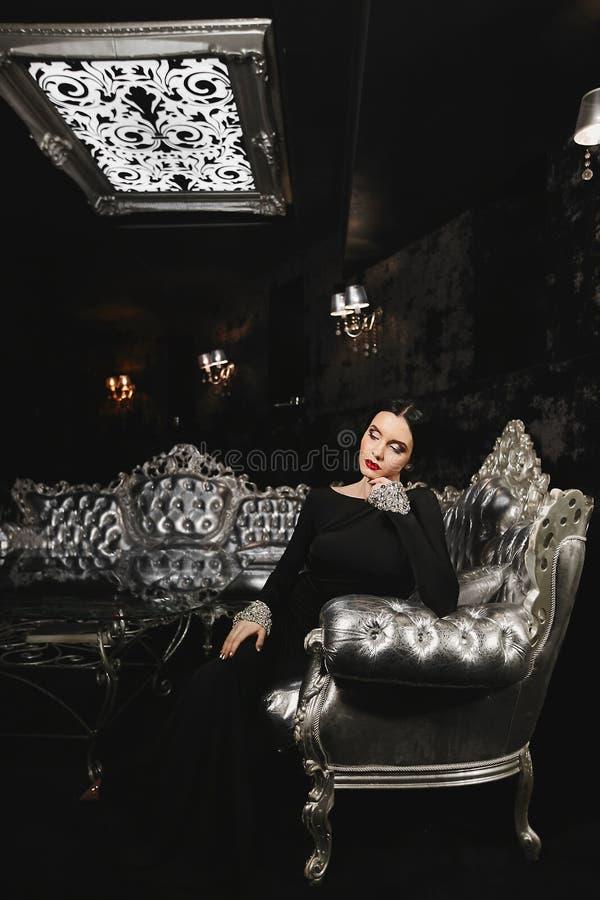 La mujer modelo morena de moda y atractiva con el cuerpo perfecto y con los labios rojos en vestido de noche negro con se sienta  fotos de archivo libres de regalías