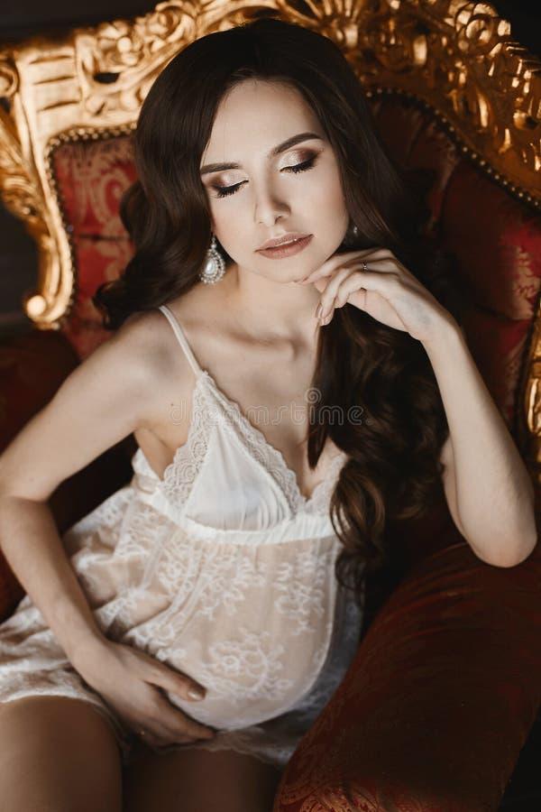 La mujer modelo morena embarazada joven sensual y hermosa con maquillaje brillante en la ropa interior blanca del cordón se sient fotografía de archivo