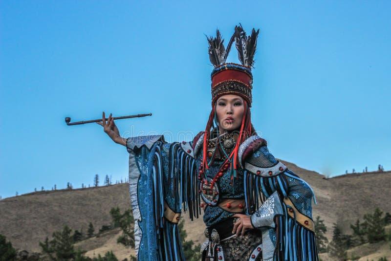 La mujer mongoloide en un traje del chamán y de la bruja baila y fuma un tubo contra la perspectiva de las montañas fotografía de archivo