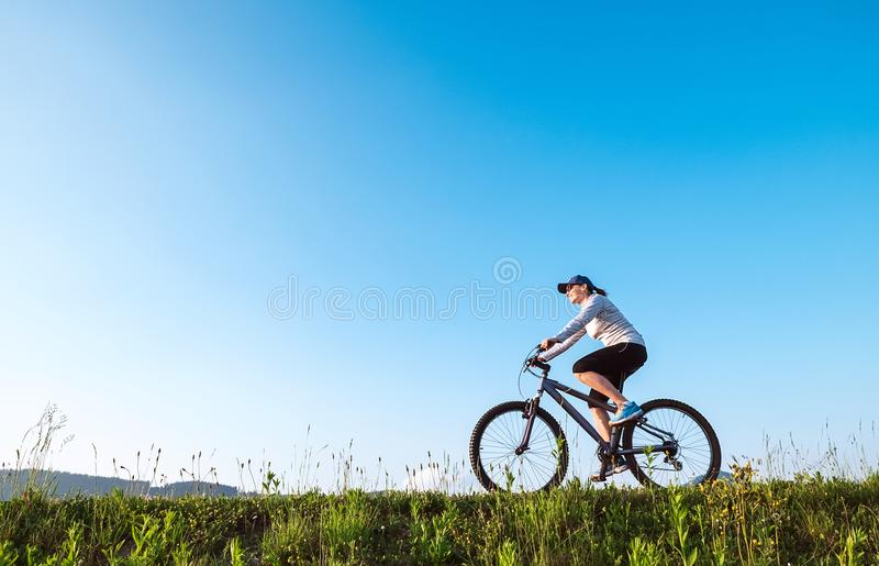 La mujer monta un bicykle por la carretera nacional imagenes de archivo