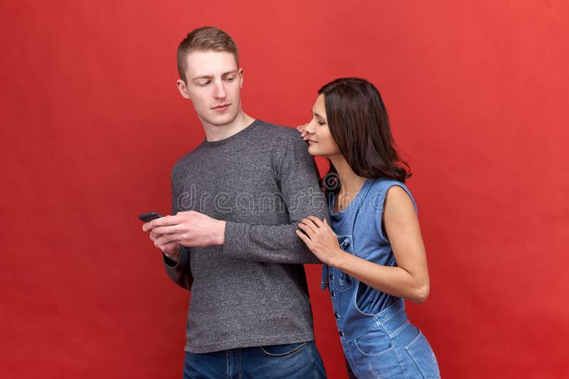 La mujer morena ardiente hermosa mira fijamente incrédulamente espiando para llamar por teléfono a su novio imagen de archivo