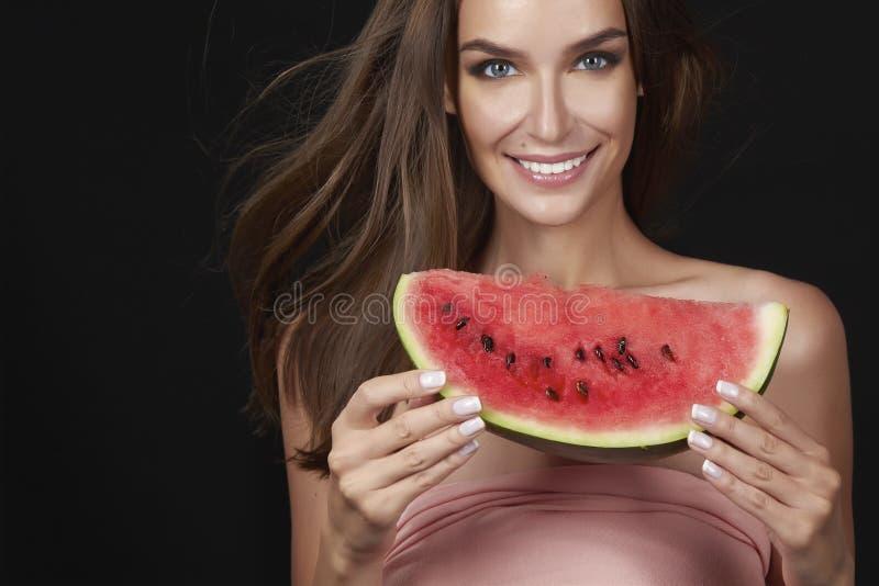 La mujer morena atractiva hermosa que come la sandía en un fondo blanco, comida sana, comida sabrosa, dieta orgánica, sonríe sano imagen de archivo libre de regalías