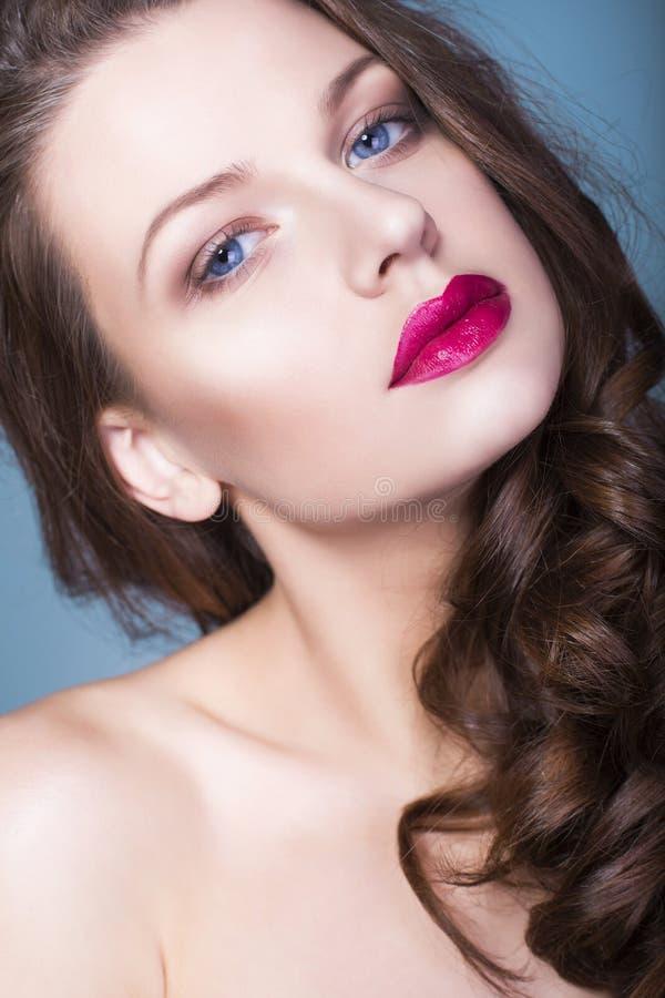 La mujer morena con creativo compone los labios rojos llenos de las sombras de ojos violetas, los ojos azules y el pelo rizado co imagenes de archivo