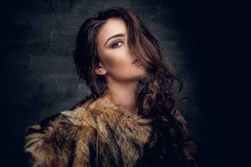 La mujer morena con el pelo rizado largo se vistió en un abrigo de pieles imagenes de archivo