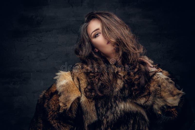 La mujer morena con el pelo rizado largo se vistió en un abrigo de pieles imagen de archivo