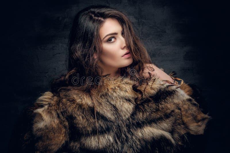 La mujer morena con el pelo rizado largo se vistió en un abrigo de pieles fotografía de archivo libre de regalías