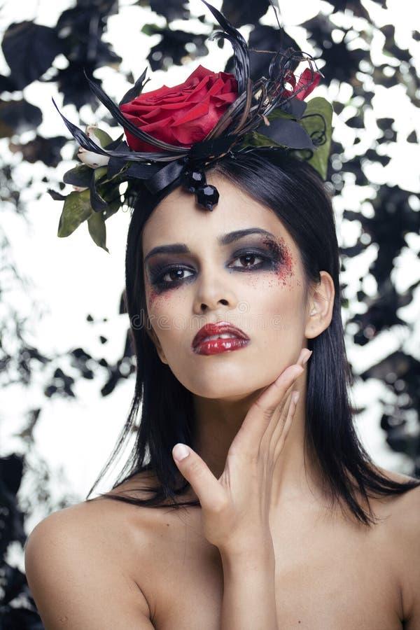 La mujer morena con joyería color de rosa, negros bonitos y el rojo, brillante componen el kike un vampiro fotos de archivo libres de regalías