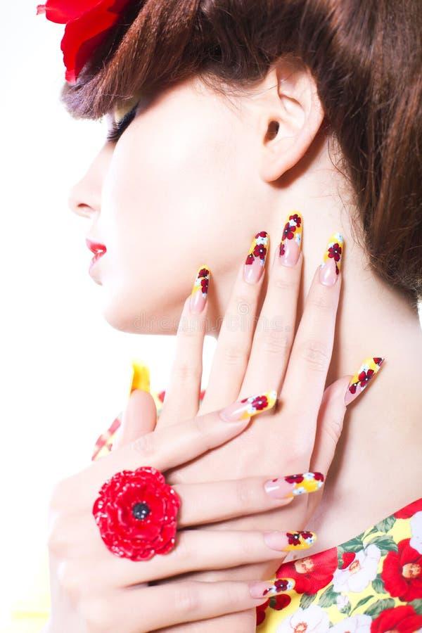 La mujer morena en vestido amarillo y rojo con la flor de la amapola en su pelo, anillo de la amapola y clavos creativos, cerró o imagen de archivo libre de regalías