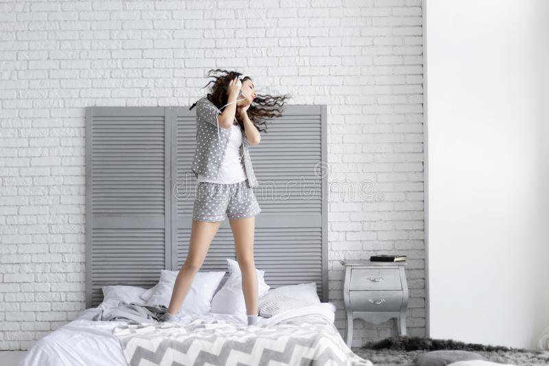 La mujer morena feliz lleva los pijamas grises Concepto de la mañana fotos de archivo