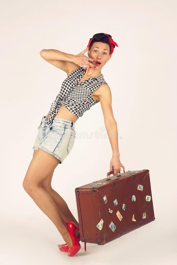 La mujer morena hermosa en perno encima de soportes del estilo y sostiene apenas una maleta pesada para el viaje, fondo blanco foto de archivo