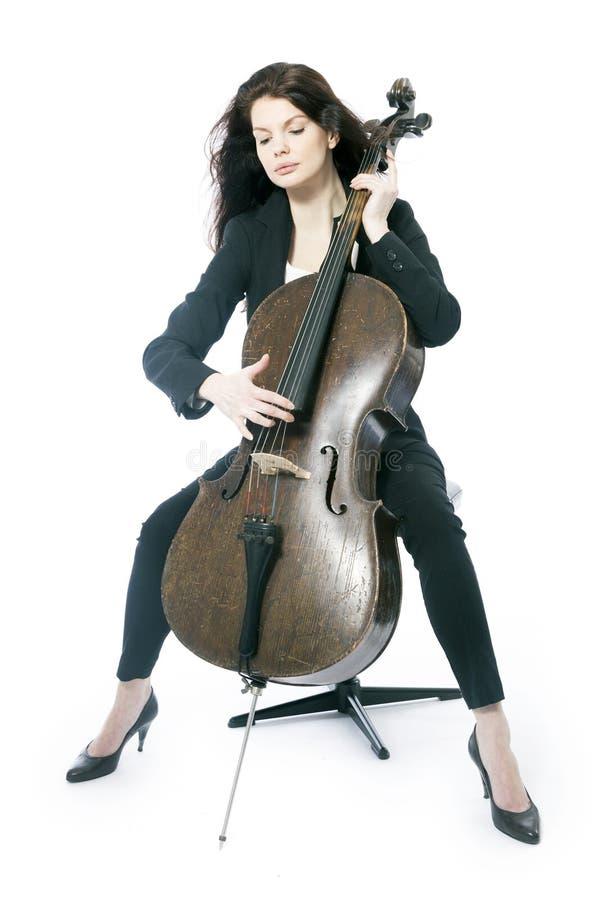 La mujer morena hermosa toca el violoncelo en estudio contra blanco imagen de archivo