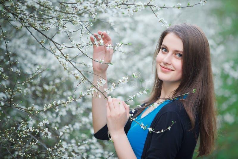 La mujer morena inhala el olor de flores imágenes de archivo libres de regalías
