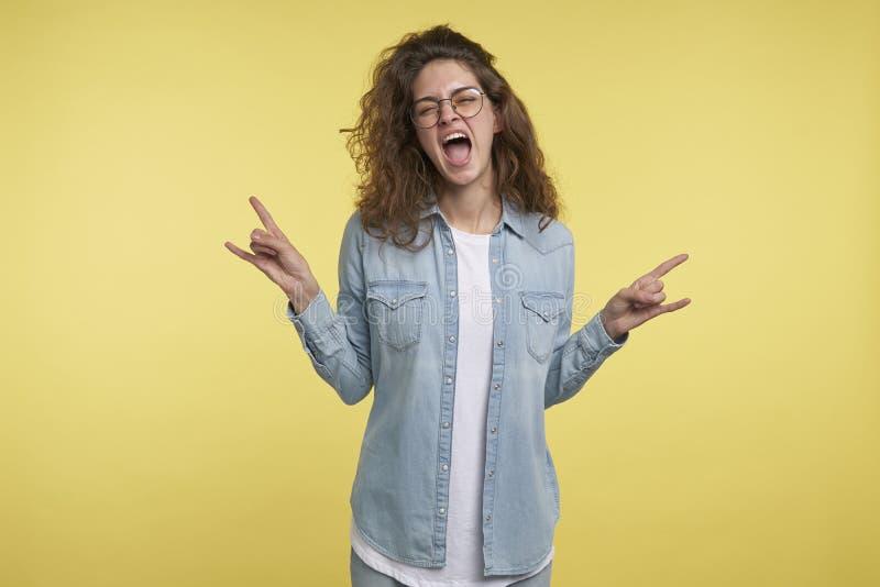 La mujer morena joven con el pelo rizado muestra la expresión loca que hace símbolo de la roca con las manos para arriba foto de archivo libre de regalías