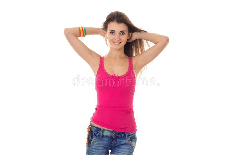 La mujer morena joven feliz en camisa rosada y vaqueros pone en cortocircuito la sonrisa en la cámara aislada en el fondo blanco imagen de archivo