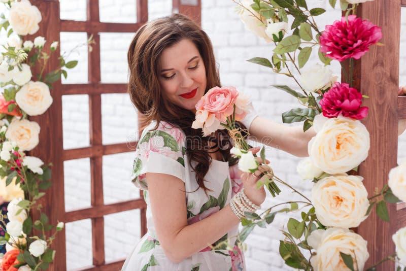 La mujer morena joven hermosa con el pelo rizado largo está oliendo las flores foto de archivo libre de regalías