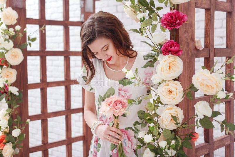 La mujer morena joven hermosa con el pelo rizado largo está presentando alrededor de arco con las flores imágenes de archivo libres de regalías