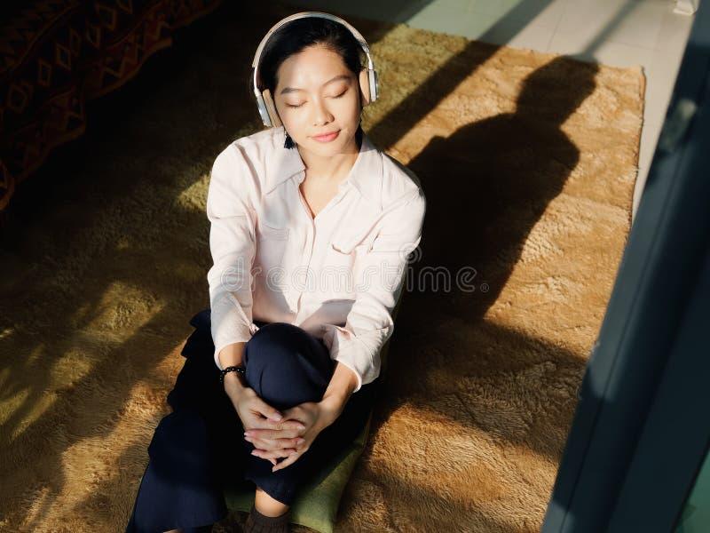 La mujer morena joven hermosa en la camisa blanca sienta y disfruta de música en día soleado en casa fotos de archivo libres de regalías