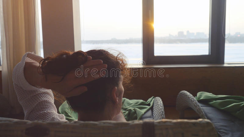 La mujer morena madura en envejecido lleva la bata blanca en el centro del balneario que miente en el té de las bebidas del sofá  fotos de archivo libres de regalías