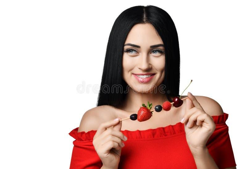 La mujer morena sonriente en vestido rojo con sholders desnudos sostiene un pequeño palillo de madera con las bayas aisladas en b fotos de archivo libres de regalías