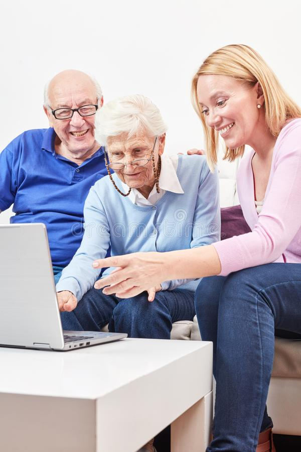 La mujer muestra a mayores en el ordenador Internet imagenes de archivo