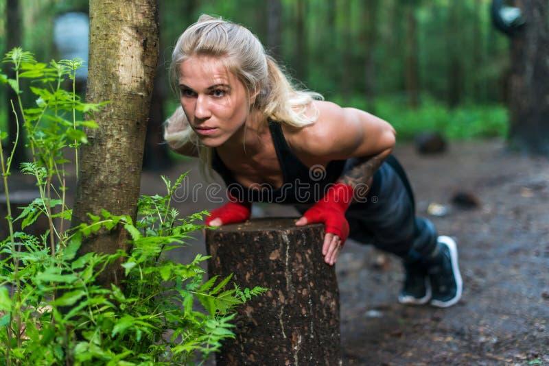 La mujer muscular que hace pectorales en la calle del parque se resuelve imagen de archivo