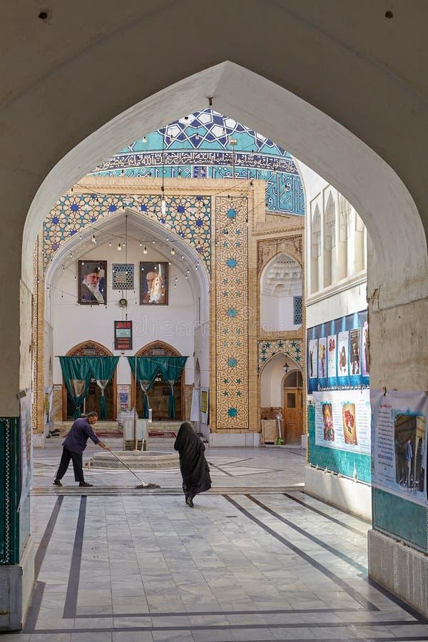 La mujer musulmán camina más allá de limpiador en el patio de la mezquita, Irán imagen de archivo