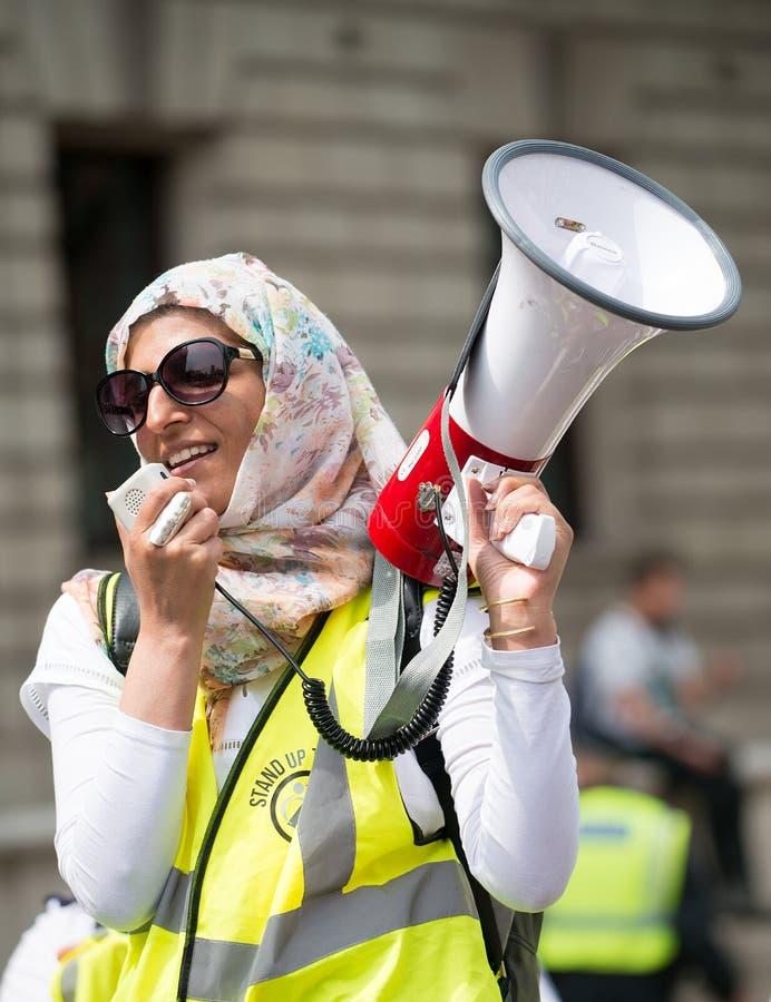 La mujer musulmán con el megáfono en la contador-versión parcial de programa del grupo de presión une contra fascismo en Whitehal foto de archivo libre de regalías