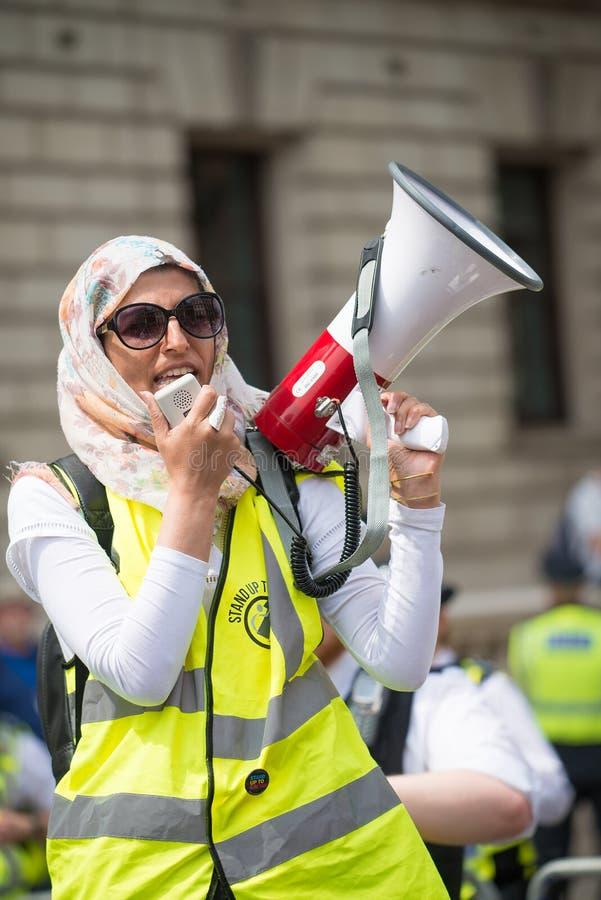 La mujer musulmán con el megáfono en la contador-versión parcial de programa del grupo de presión une contra fascismo en Whitehal imagen de archivo