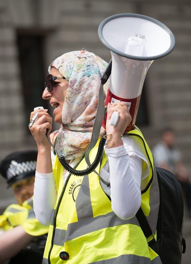 La mujer musulmán con el megáfono en la contador-versión parcial de programa del grupo de presión une contra fascismo en Whitehal fotos de archivo