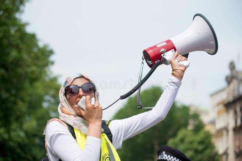 La mujer musulmán con el megáfono en la contador-versión parcial de programa del grupo de presión une contra fascismo en Whitehal foto de archivo