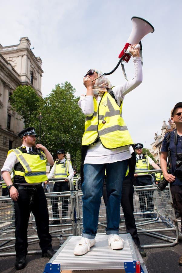 La mujer musulmán con el megáfono en la contador-versión parcial de programa del grupo de presión une contra fascismo en Whitehal imágenes de archivo libres de regalías