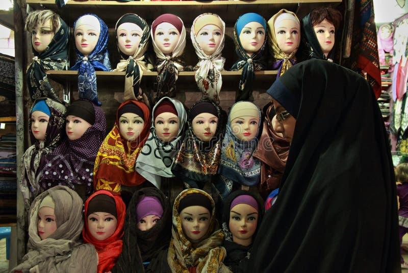 La mujer musulmán joven delante de las bufandas del bazar se coloca fotos de archivo